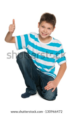 A handsome boy in striped shirt holding his thumb up on the white background - stock photo