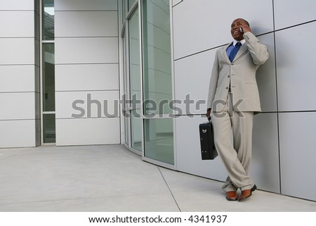 A handsome business man on the phone outside his office