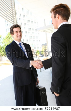 A handsome business man team  shaking hands outside office - stock photo