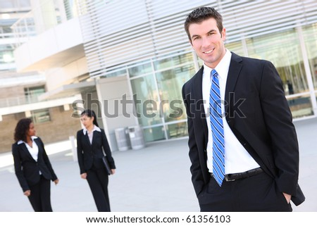A handsome business man with team in background at office building