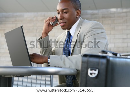 A handsome business man working on his laptop computer - stock photo