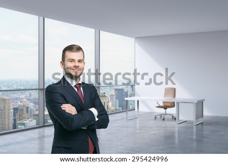 A handsome businessman in a workplace at modern corner panoramic office in New York, Manhattan. A concept of financial consulting services. - stock photo