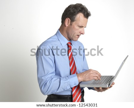 A handsome businessman working on his laptop - stock photo