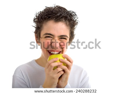 A handsome Caucasian boy wearing a long sleeved white shirt is goingt to bite and eat a yellow apple with both hands while laughing - stock photo