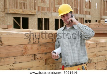 A handsome construction worker on the job and on the phone - stock photo