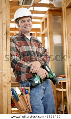 A handsome construction worker on the job-site with his tools, ready to work.  Authentic and accurate content depiction. - stock photo
