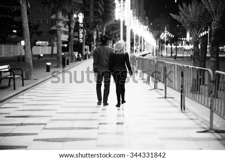 A handsome couple on a date night walk in the city. Black and white photo - stock photo