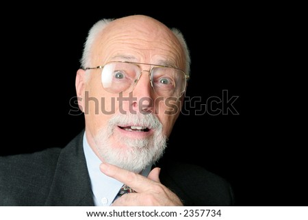 A handsome, distinguished looking senior man on a black background looking surprised. - stock photo