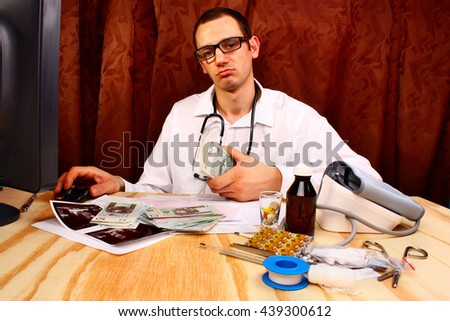 A handsome doctor holding polish money in doctor's office