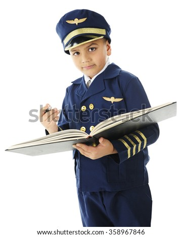 """A handsome elementary """"airline pilot"""" looking at the viewer as he prepares to sign the opened logbook.  On a white background. - stock photo"""