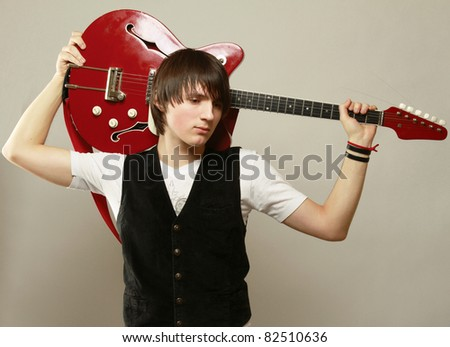 A handsome guitar player, isolated on grey - stock photo