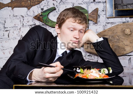 A handsome guy in the restaurant looks out on the sushi - stock photo