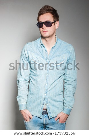 a handsome guy with glasses and a denim shirt with a grey background