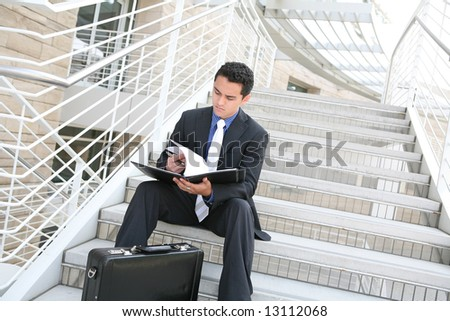 A handsome hispanic business man on the stairs reviewing his notes - stock photo