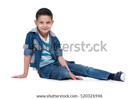 A handsome little boy sits on the white background