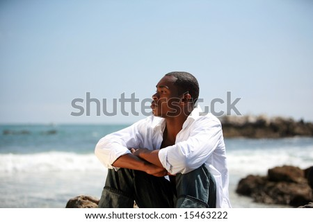 a handsome male model enjoys a summer day at the beach - stock photo