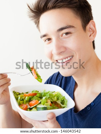 A handsome man eating salad - stock photo