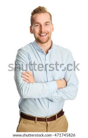A handsome man in his 20s standing against a white background, wearing a blue shirt tucked in to his khaki pants. Smiling towards camera.