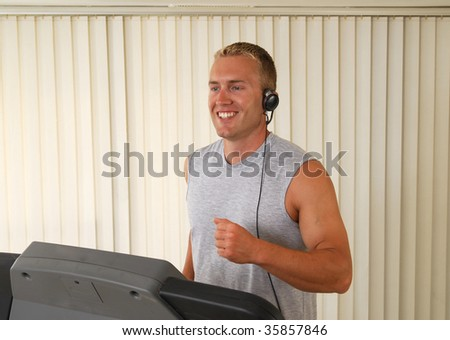 A handsome man running on a treadmill - stock photo