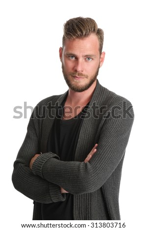 A handsome man standing with a white background wears a grey sweater and a black t-shirt. Feeling good with a smile on his face.