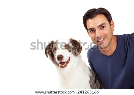 A handsome man with dark hair sitting next to a cute Border Collie dog. Closeup photo with room for copy. - stock photo