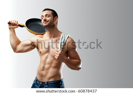 A handsome muscular cook posing with a pan on his shoulder on a neutral background with space for text - stock photo