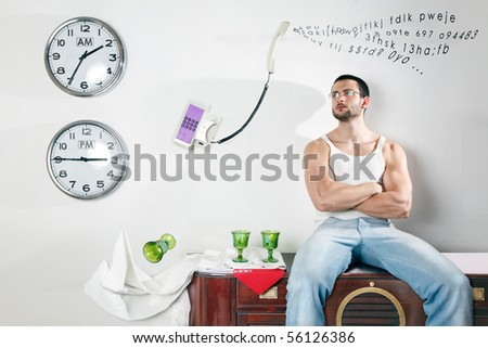 A handsome muscular man sitting on furniture watching a telephone talking nonsense in a surreal scene.