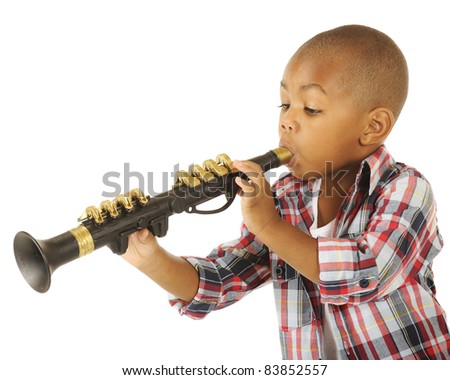 A handsome preschooler blowing his toy clarinet.  Isolated on white. - stock photo