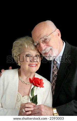 A handsome, romantic, senior couple holding a red rose, posing against a black background. - stock photo