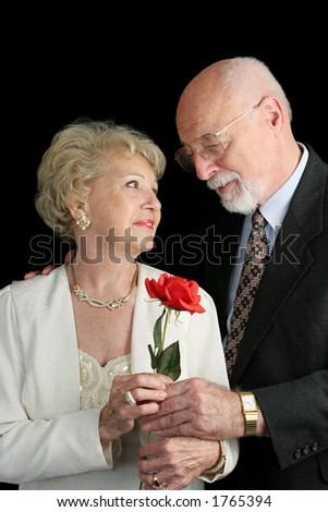 A handsome senior couple in love.  He's giving her a rose.  A hearing aid is visible in her ear. - stock photo
