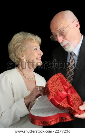 A handsome senior man giving a valentine gift to his beautiful wife.  Black background. - stock photo