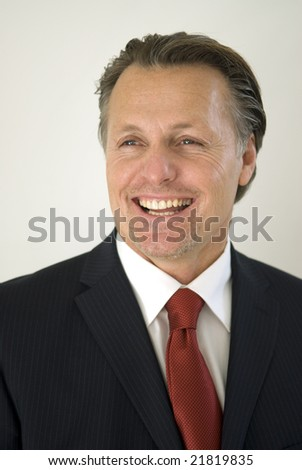 A handsome smiling businessman  is looking away with a gorgeous smile - stock photo