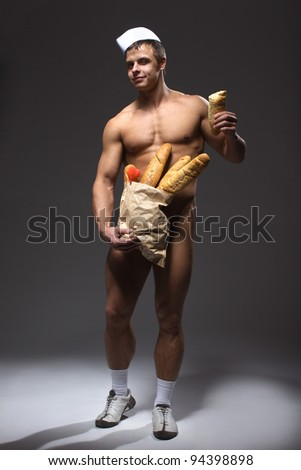A handsome smiling man with bodybuilder physique holding a brown paper bag of baguettes concealing his loins, implied nude. - stock photo