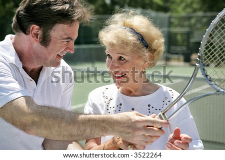 A handsome tennis pro gives pointers to a beautiful older lady.