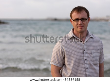 A handsome 35-year-old man in the background of the sea - stock photo