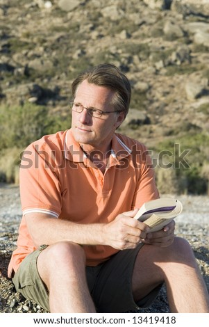 A handsome 44 year old man wearing spectacles and holding a book on the beach.