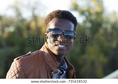 A handsome young black man in sunglasses and a leather jacket on a fall day