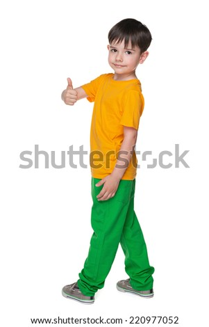 A handsome young boy with his thumb up looks back - stock photo