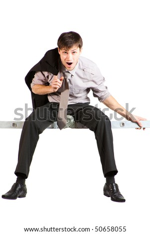 A handsome young businessman with jacket over the shoulder, rolled-up sleeves sitting high on ladder and screaming. Vertical shot. Isolated on white. - stock photo