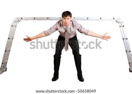 A handsome young businessman with rolled-up sleeves stands in ladder gates with spread hands as a goalkeeper. Horizontal shot. Isolated on white. - stock photo