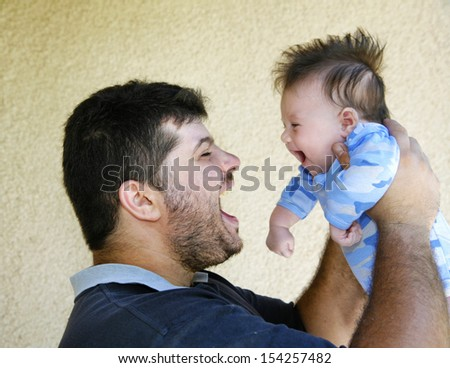 A handsome young father playing with his cute little son - stock photo