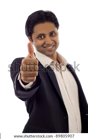 A handsome young Indian businessman showing thumbs up sign isolated over white background - stock photo