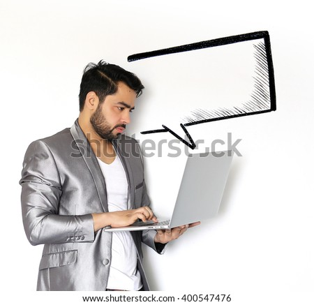 A handsome young Indian man chatting on laptop against a white background - stock photo