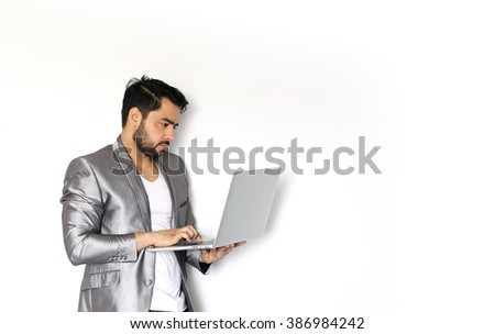 A handsome young Indian man working on laptop against a white background - stock photo