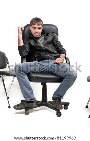 a handsome young man bad guy Caucasian sitting in a leather jacket to a leather chair and shows everything is fine, isolated over white, cool smile