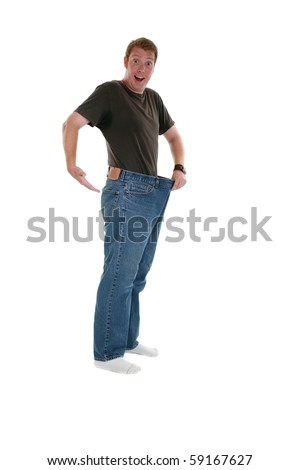 A handsome young man showing how much weight he lost, isolated on white - stock photo