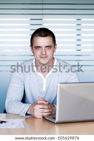 A handsome young man sitting at the table with a laptop - stock photo