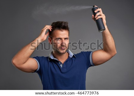 A handsome young man smiling while fixing his hair with a hairspray.