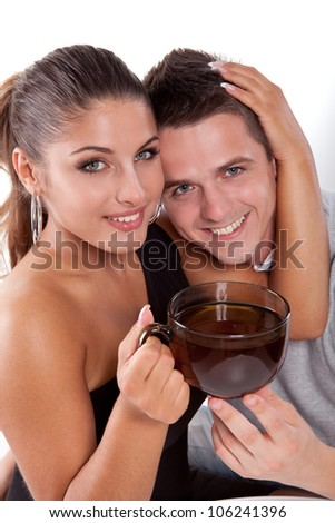 A handsome young man with a beautiful woman with a large cup of tea - stock photo