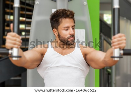 A handsome young muscular sports man doing butterfly exercise
